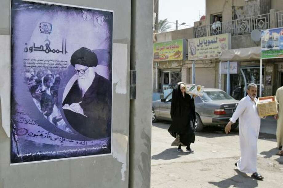 A poster featuring a photo of Grand Ayatollah Mohammad Sadiq al-Sadr, the late father of anti-U.S. cleric Muqtada al-Sadr, prohibits the use of arms by the Mahdi Army during negotiations. Photo: KARIM KADIM, ASSOCIATED PRESS