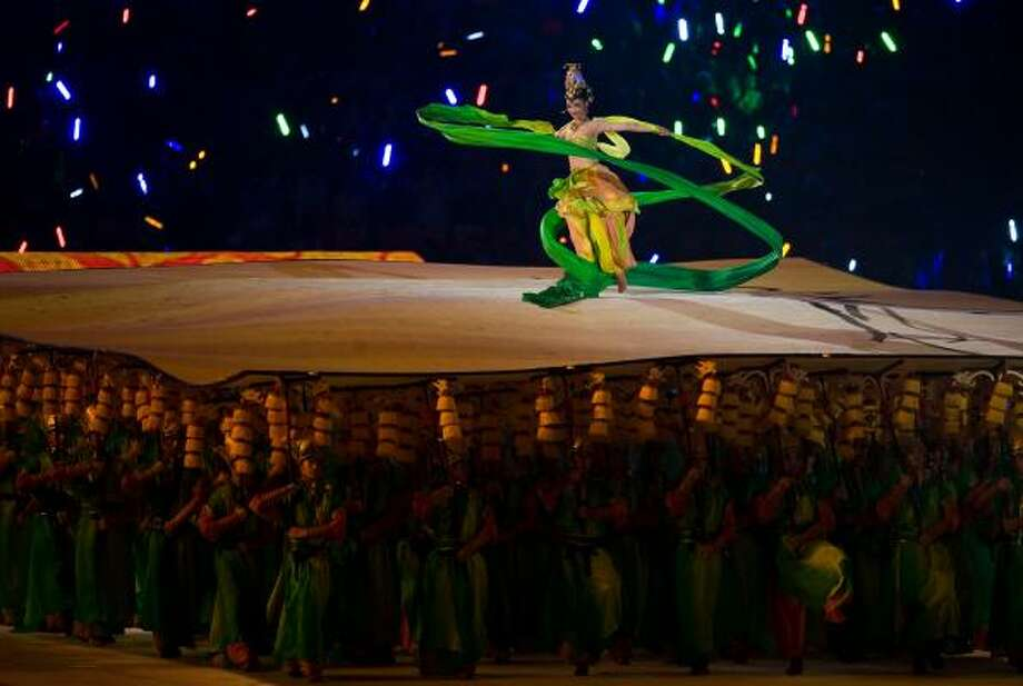 Performers support a dancer during the Olympic Games opening ceremony in Beijing on Friday. Photo: SMILEY N. POOL, CHRONICLE