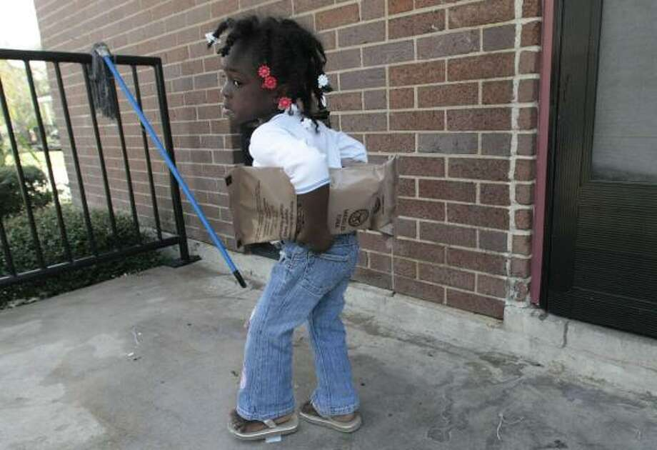 Jahnae' Nealy, 3, totes packaged food her family picked up Wednesday at a Texas Southern University aid distribution site. Photo: BILLY SMITH II, CHRONICLE