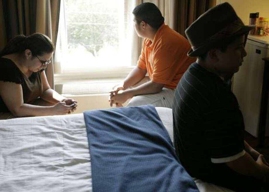 Elizabeth Galvan, left, and sons Richard and Alex pass the time in a hotel room while waiting for power to be restored to their apartment. Area hotels are likely at 95 percent capacity, said Joan Johnson of the Hotel & Lodging Association of Greater Houston. Photo: ERIC KAYNE, CHRONICLE