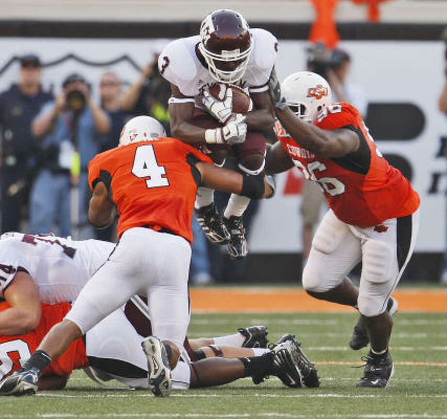 Mike Goodson is halted by Oklahoma State defenders. Photo: Sue Ogrocki, AP