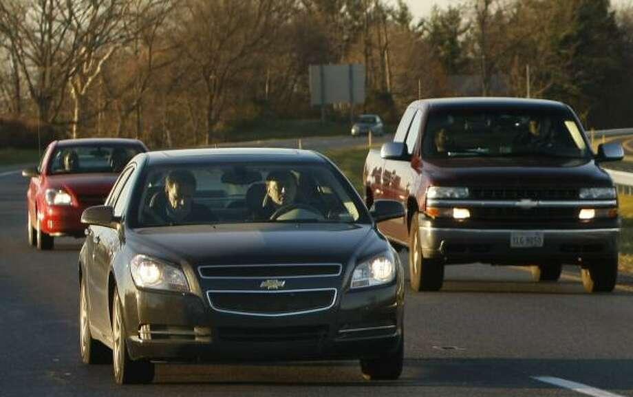 CEO Rick Wagoner of GM, left, traveled 500 miles in a Chevrolet Malibu hybrid to Washington, D.C. Photo: GERALD HERBERT, ASSOCIATED PRESS