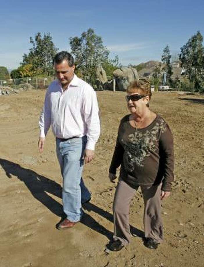 "Sean Walsh, left, and his mother Patricia Walsh plan to rebuild her San Diego home, which was destroyed by wildfires, using funds from ""green"" insurance programs. Photo: DENIS POROY, ASSOCIATED PRESS"