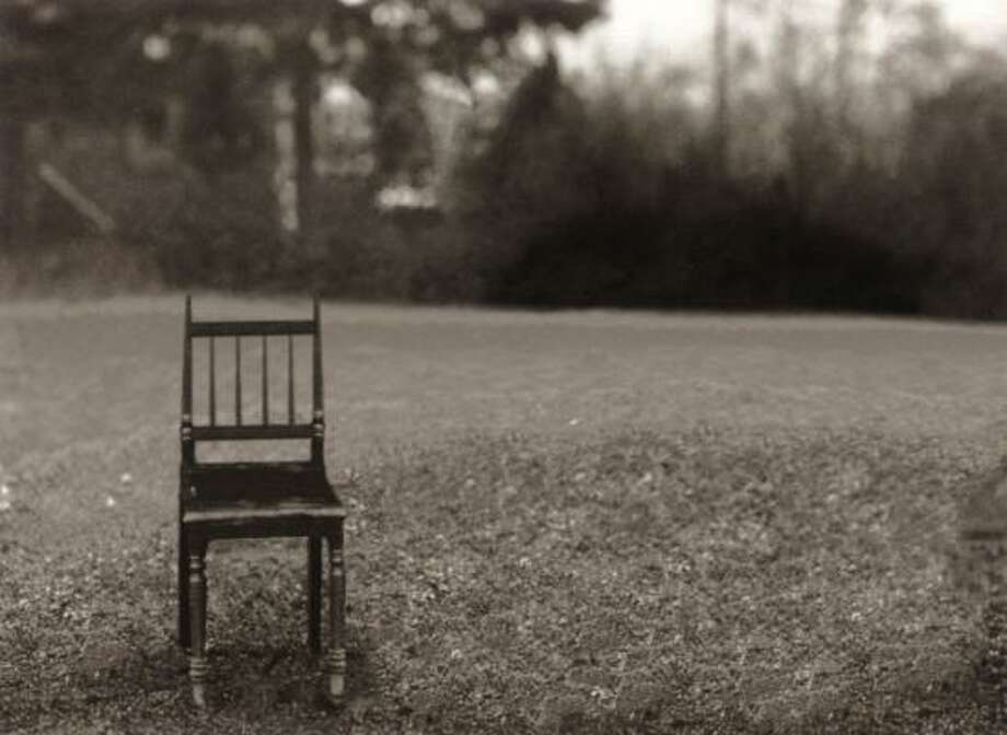 A lone chair appears abandoned on a grassy lawn in Working Class Family. Once, in German photographer August Sander's time, a father sat in it, surrounded by his large family. Photo: MICHAEL SOMOROFF, Michael Somoroff