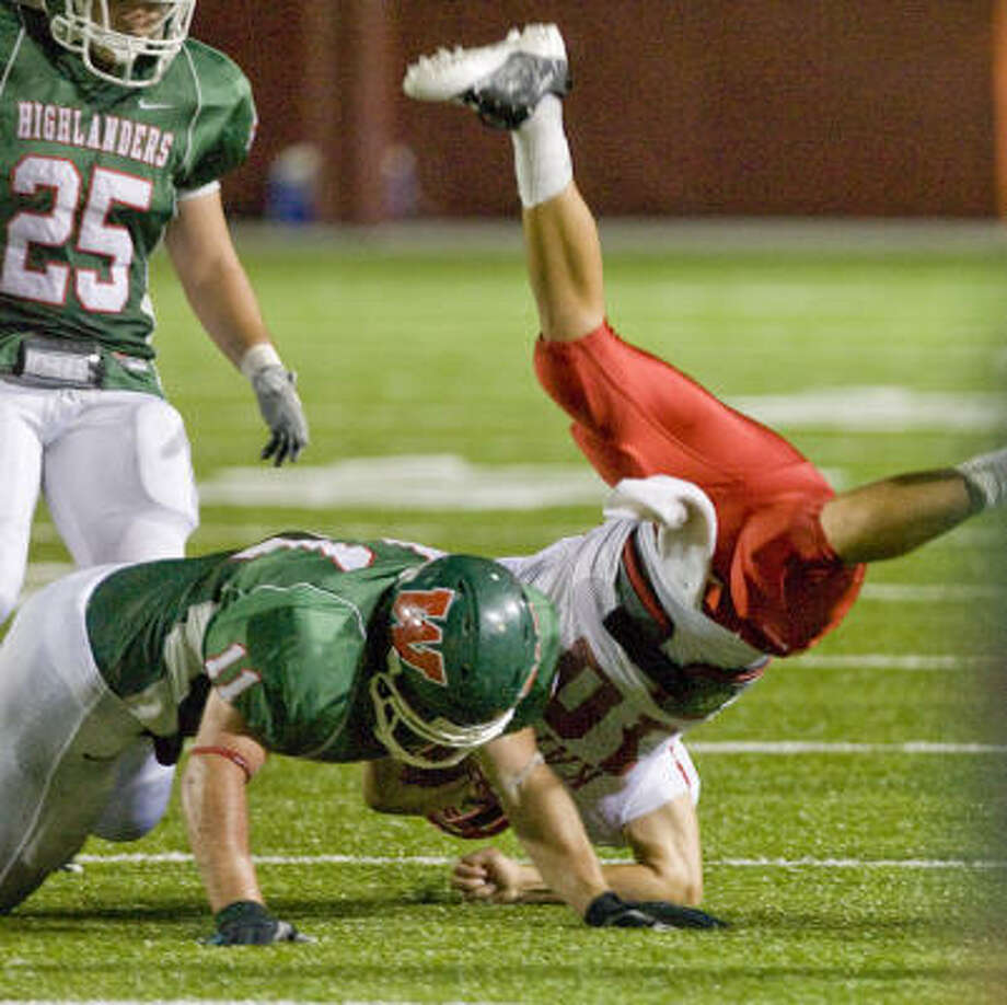 Katy quarterback Parker Ray is upended by The Woodlands' Robert Bouthilet in the first half of Katy's 47-0 loss. Photo: Steve Campbell, Houston Chronicle