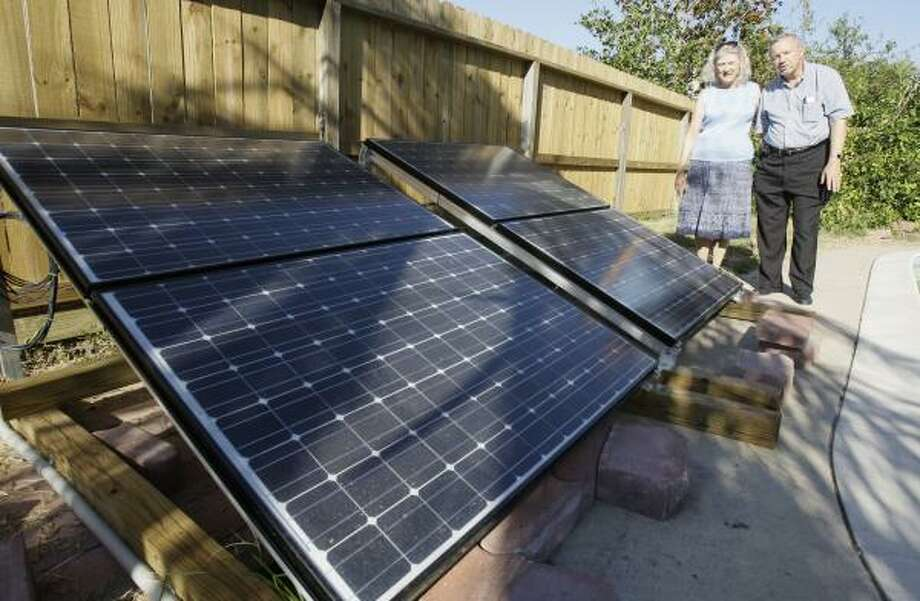 Patricia and Milton Cecalek with the solar panels that run their SolCool air-conditioning system at their Pearland home. Photo: MELISSA PHILLIP, CHRONICLE