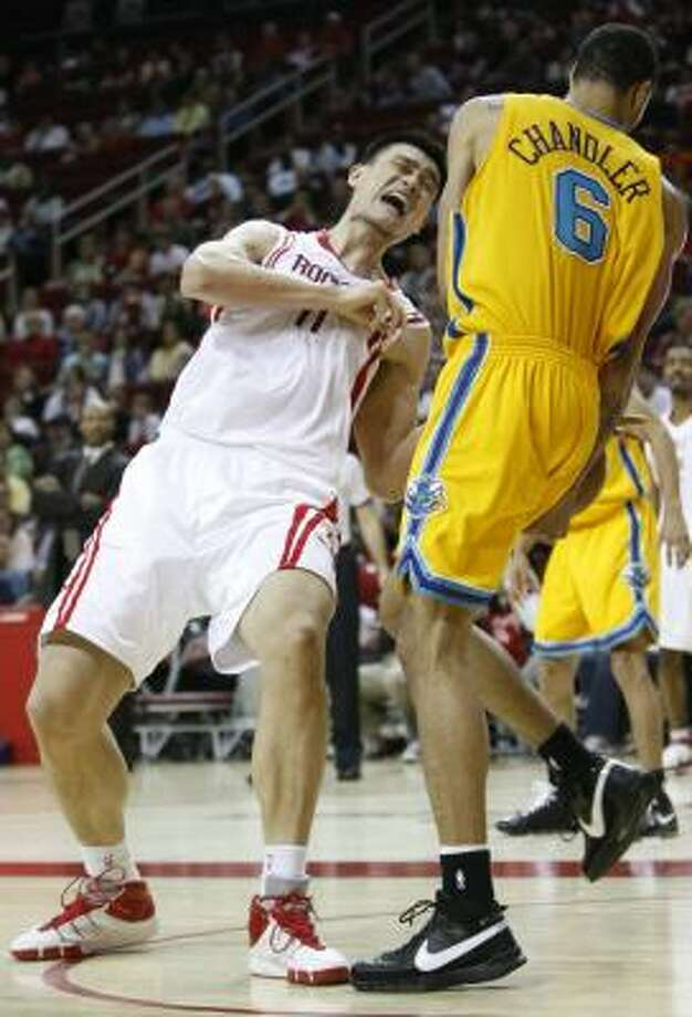 Yao Ming, who did his part with 30 points and 16 rebounds, feels the effects of a foul by the Hornets' Tyson Chandler. Photo: KEVIN FUJII, CHRONICLE