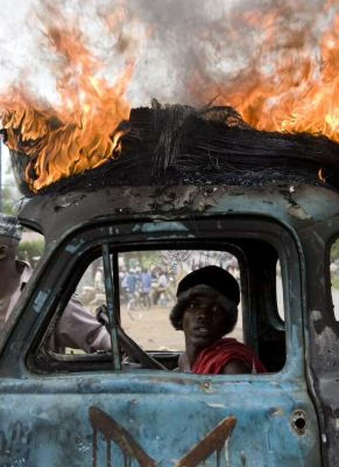 A Luo tribesman sits in a vehicle with a burning tire on the roof in the Kenyan town of Kisumu. Photo: YASUYOSHI CHIBA, AFP/GETTY IMAGES