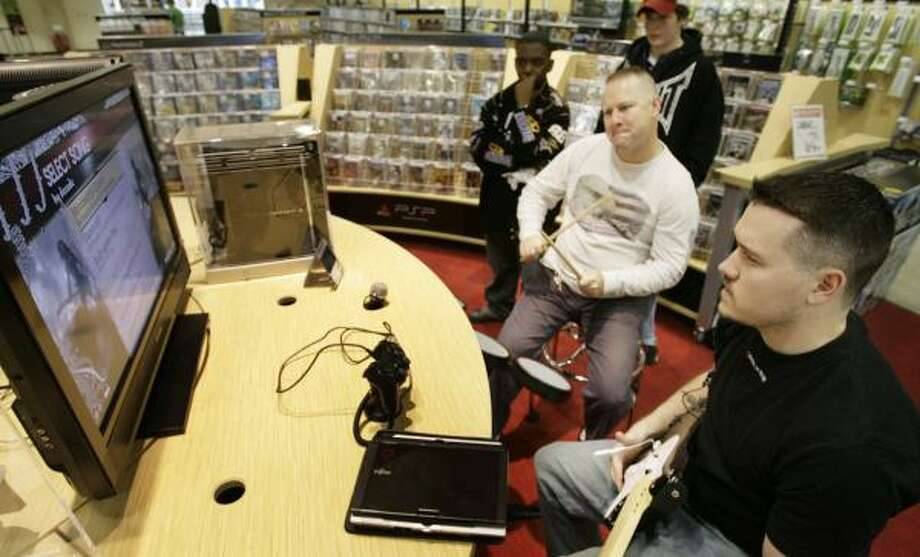 Jarrion Turner, left, Justin Hughes, Dean Peterson and salesman David Goss play and watch Mississippi Queen on the game Rock Band at Circuit City's new concept store, City, in Humble. The store is designed to be smaller than a traditional Circuit City. Photo: ERIC KAYNE PHOTOS, CHRONICLE