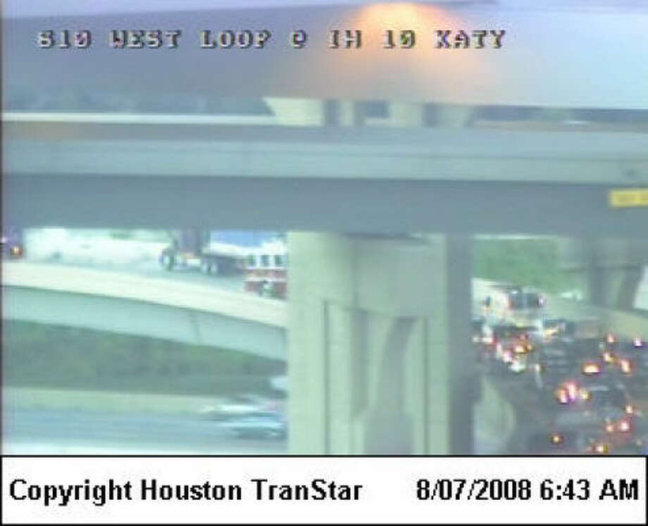 An overturned truck is partially blocking the ramp from the southbound West Loop to the eastbound Katy Freeway. Photo: Houston TranStar