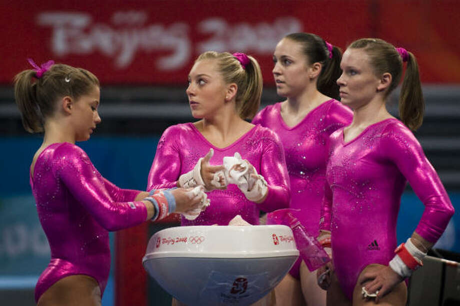 The U.S. gymnasts get ready before a workout on the uneven bars. Photo: Smiley N. Pool, Chronicle