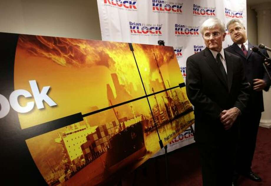Congressional candidate Brian Klock, right, and supporter Bob Perry show Klock's campaign billboard, depicting Houston under siege. Photo: ERIC KAYNE, CHRONICLE