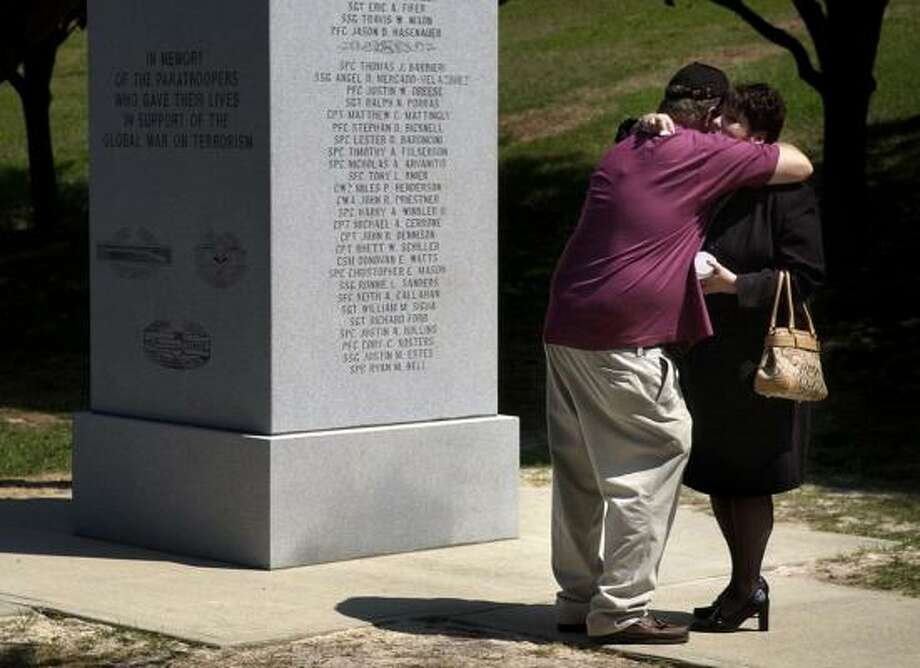 Skip and Rhonda Rollins embrace in front of the Army's 82nd Airborne Division memorial, where their son's name, Spc. Justin Rollins, is engraved in May 2007. The wall is now being expanded for more names. Photo: STEPHENIE BRUCE, THE FAYETTEVILLE OBSERVER