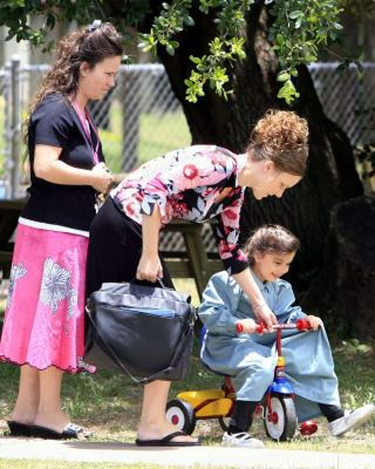 Two women lead a young FLDS member to a car at the Kidz Harbor group home Tuesday in Liverpool. There were many firsts for the children: first hula hoop, first bicycle, seeing a dog and humidity.