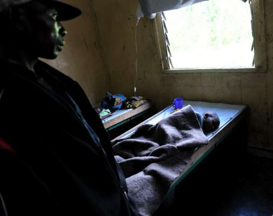A man watches over a child sick with cholera at the main hospital in the North Kivu provincial capital of Goma on Sunday. Some fear an epidemic is taking place in the region as fighting hinders access to the area. Photo: ROBERTO SCHMIDT, AFP/GETTY IMAGES