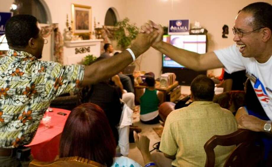 Jerome Kendrick , left, and Mark Wimberly give each other a high five as Barack Obama appears on TV during Thursday's party in Katy for the political group Miracles Can Happen. Photo: NICK De La TORRE, CHRONICLE