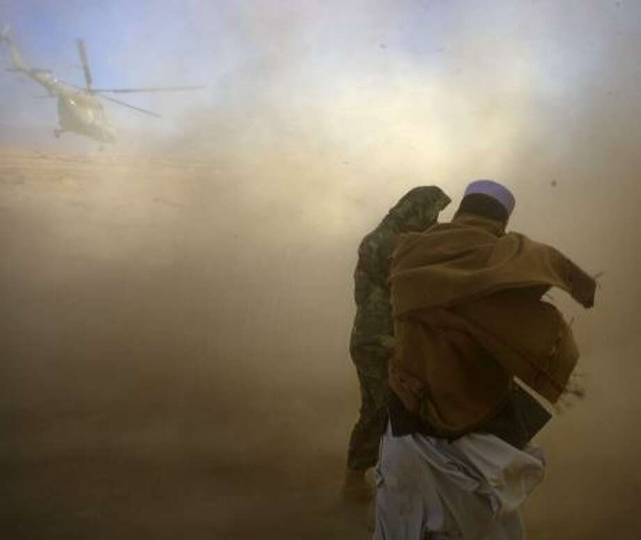 Afghan civilians shield themselves from dust and debris as an Afghan National Army helicopter flies overhead near a base in Paktika province, situated at the restive border with Pakistan. Photo: DAVID FURST, AFP/GETTY IMAGES