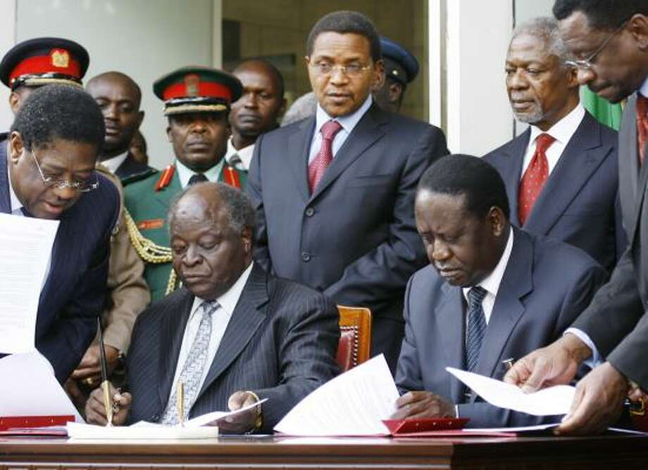 President Mwai Kibaki, seated at left, and opposition leader Raila Odinga sign the agreement Thursday in Nairobi, Kenya. Ethnic violence that followed the election two months ago killed more than 1,000. Photo: JEROME DELAY, ASSOCIATED PRESS