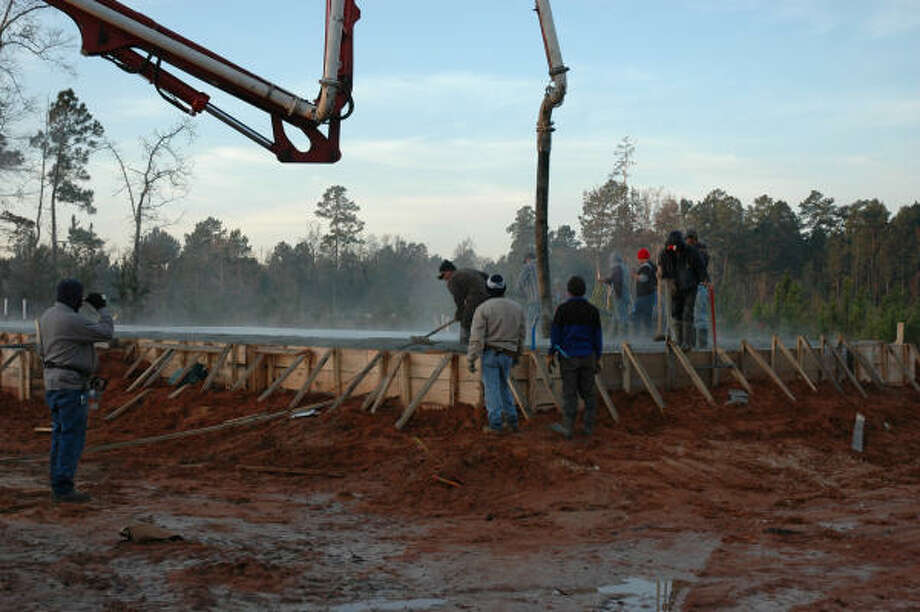 In this submitted photo, workers spread cement mix for the foundation of Woodforest's Welcome Lodge, the first structure to be built in The Johnson Development Corp.'s master-planned community near Conroe. Photo: Submitted Photo