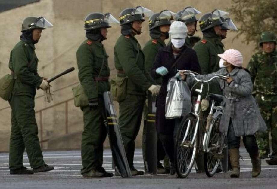 Chinese residents walk past military officers in anti-riot gear in western China's Gansu province. A strong security presence is being maintained in Tibetan areas after violent protests. Photo: NG HAN GUAN, ASSOCIATED PRESS