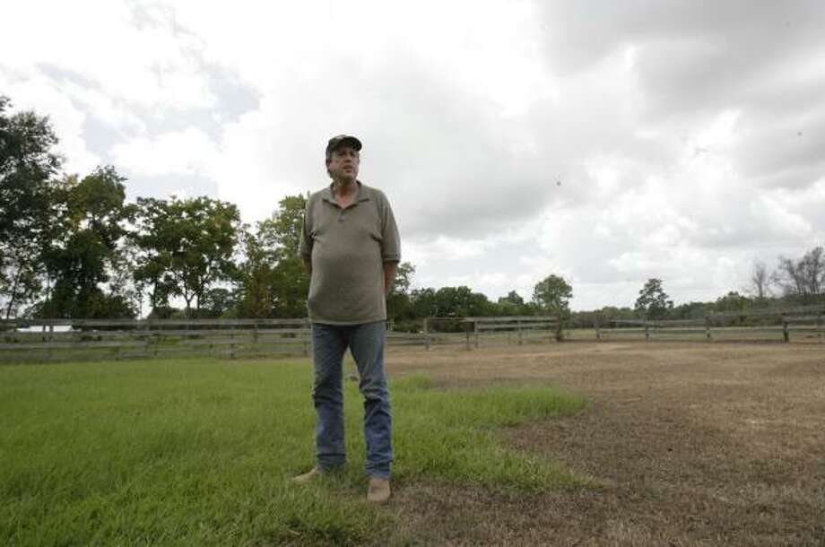 Daisetta Mayor Lynn Wells stands in his yard, where salt water began gushing from an abandoned well not long after the sinkhole began to form. Much of the vegetation was killed, and the land was flooded until the well was capped. Photo: JULIO CORTEZ PHOTOS, CHRONICLE