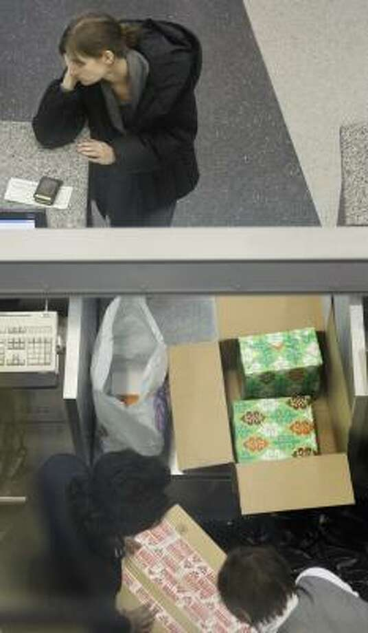 A passenger at an American Airlines ticket counter waits as her wrapped Christmas presents are boxed up to be checked as baggage at Chicago's O'Hare International airport Wednesday. Photo: M. Spencer Green, AP