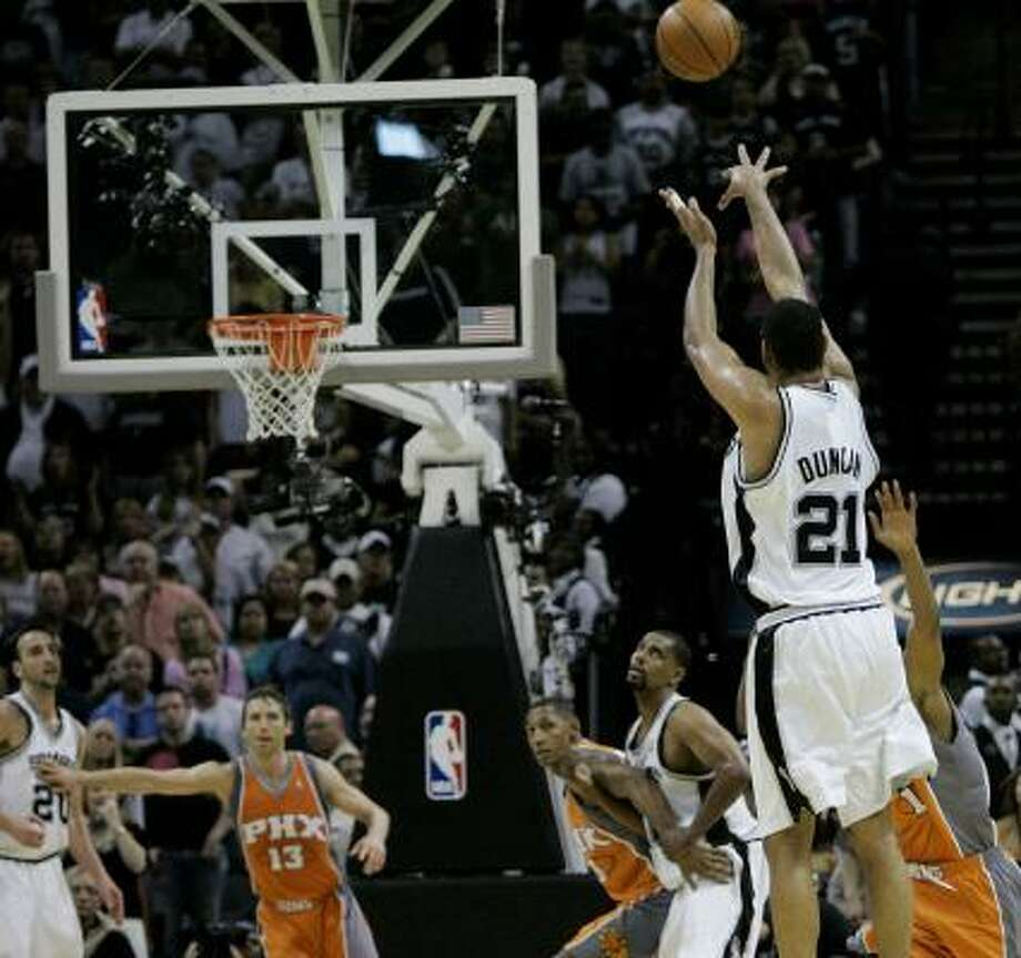 Tim Duncan launches the 3-pointer that tied the game at the end of the first overtime (left), then celebrates after it went through during the Spurs' win Saturday. Photo: Eric Gay, AP