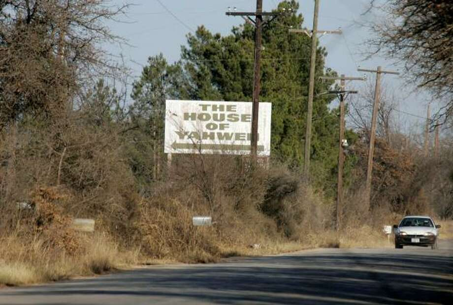 A car drives past a sign pointing toward the House of Yahweh in a rural area near Clyde in West Texas. Authorities charged the group's leader, Yisrayl Hawkins, with performing polygamous weddings and forcing children to work at the compound. Photo: Donna McWilliam, Associated Press