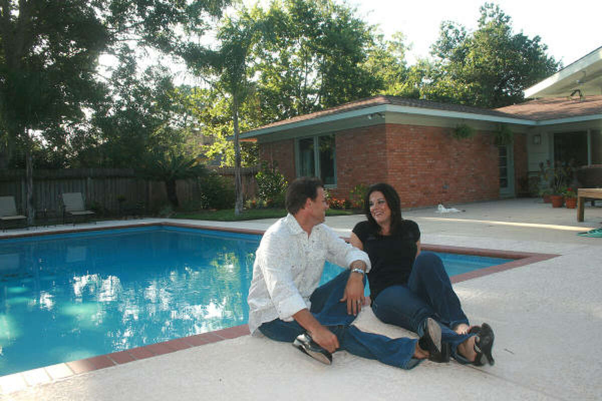 Chris and Lindsey Kimble enjoys the morning sun briefly in the the backyard pool at their newly renovated home in the Glenbrook Valley subdivision near Hobby Airport.