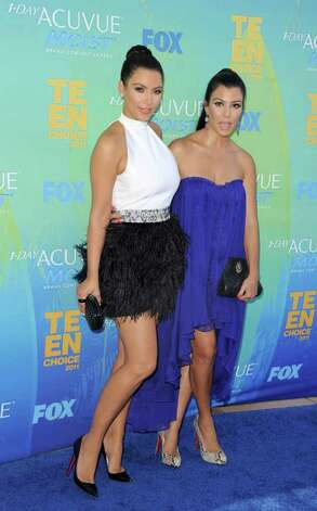 TV personalities Kim Kardashian and Kourtney Kardashian arrive at the 2011 Teen Choice Awards held at the Gibson Amphitheatre in Universal City, California. Photo: Jason Merritt, Getty Images / 2011 Getty Images