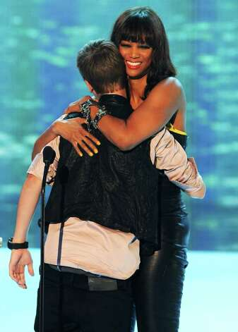 Singer Justin Bieber (L) and TV personality Tyra Banks onstage during the 2011 Teen Choice Awards held at the Gibson Amphitheatre in Universal City, California. Photo: Kevin Winter, Getty Images / 2011 Getty Images