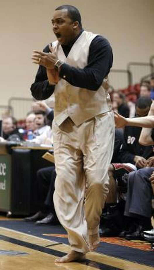 IUPUI coach Ron Hunter walks barefoot on the sidelines as his team battles Oakland University Thursday. Hunter coached barefoot to raise awareness for needy children, with a goal of sending 40,000 pairs of shoes to Africa. Photo: AJ Mast, AP