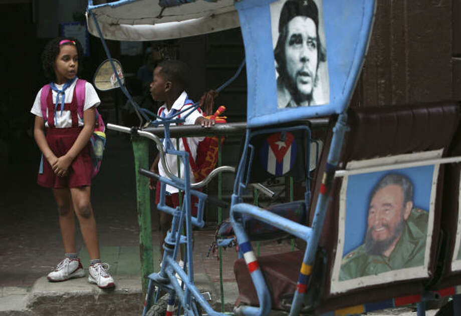 "Children stand next to a bicytaxi decorated with photographs of Cuban leader Fidel Castro, right, and Cuban revolutionary hero Ernesto ""Che"" Guevara in Havana on Tuesday. Photo: Ariana Cubillos, Associated Press"