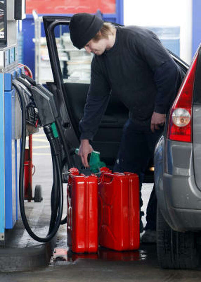 A man fills up jerrycans at the Esso petrol station in Edinburgh, Scotland, on Friday. Stations in and around Edinburgh were limiting gas purchases to $40 per visit on Saturday. Photo: Danny Lawson, Associated Press