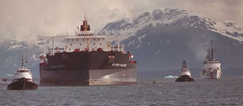 Escorted by a Coast Guard cutter, the Exxon Valdez is under tow on June 23, 1989. Photo: AL GILLO, ASSOCIATED PRESS FILE
