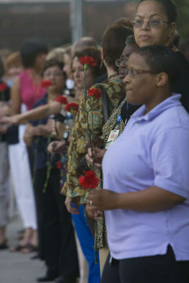 Holding red carnations, mourners line the streets outside Texas Children's Hospital for the funeral procession for Dr. Ralph Feigin Monday. Photo: James Nielsen, Chronicle