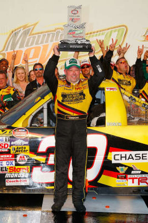 Todd Bodine hoists his trophy in Victory Lane after winning the NASCAR Craftsman Truck Series Mountain Dew 250 at Talladega. Photo: John Harrelson, Getty Images For NASCAR