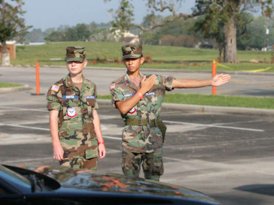 Civil Air Partol Cadet Airman First Class Matt Horton, left, observes as Cadet Technical Sergeant Alex Barrett directs the first of 1,400 cars to receive supplies on Sept. 21 at the Hope and the First Assembly of God Church of Humble.