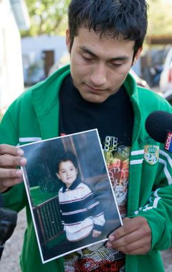 Pedro Armendarez, 18, holds a photo of his brother Cesar Armendarez, 9, who was killed Wednesday. Photo: Steve Campbell, AP