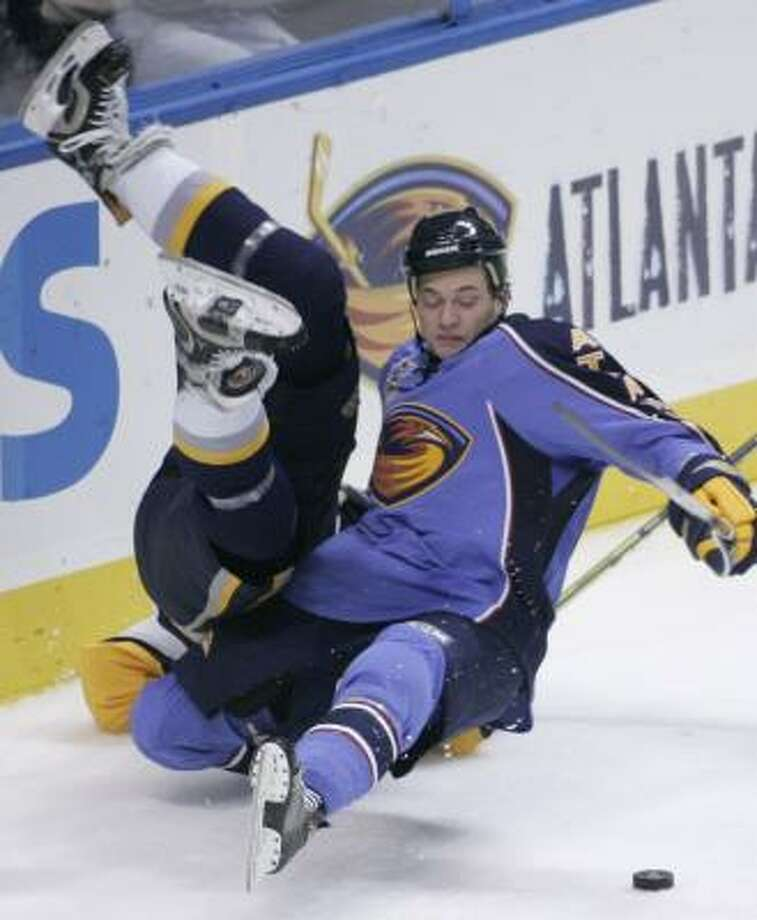 The Sabres' Andrew Peters, left, and the Thrashers' Kevin Doell hit the ice after a run-in during the third period. Photo: JOHN AMIS, ASSOCIATED PRESS