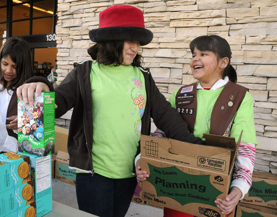 Brownies Dorothy Rodarte and Lizbeth Martinez stack boxes of cookies during the Brownie Troop 10213 Girl Scout Cookie Sale at Hastings Books, Music and Video in Conroe on March 7. Photo: David Hopper, For The Chronicle