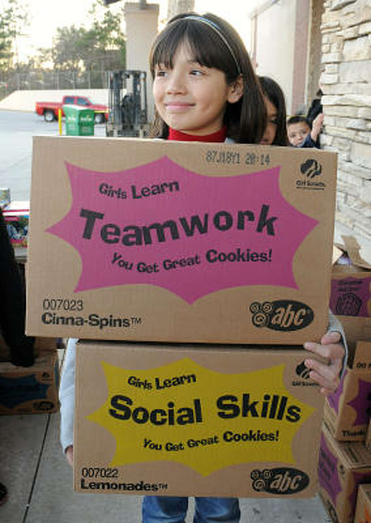 Brownie Amber Sanchez carries boxes of cookies at the recent Brownie Troop 10213 Girl Scout Cookie Sale at Hastings Books, Music and Video in Conroe.