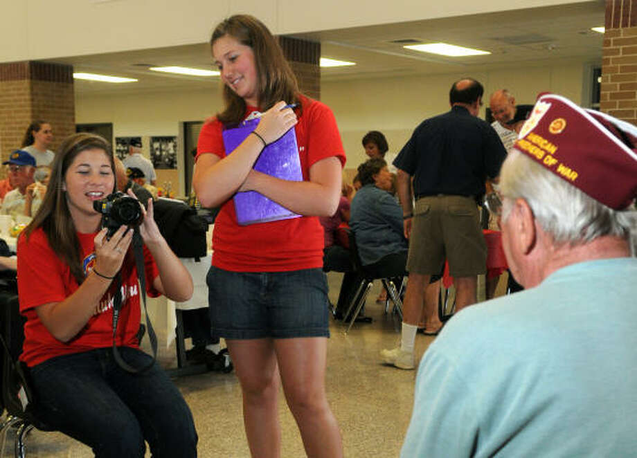 Rachel Sload, 17, left, and Claire Zolkowski, 17, both juniors at Montgomery High School, take a photo of WWII veteran Renny Kampstra, of April Sound, during a fundraiser for the Montgomery Lone Star Honor Flight program at Montgomery Junior High School. The Lone Star Honor Flight program is a national program that flies World War II veterans to Washington, D.C. to see the WWII Memorial. Photo: Jerry Baker, For The Chronicle