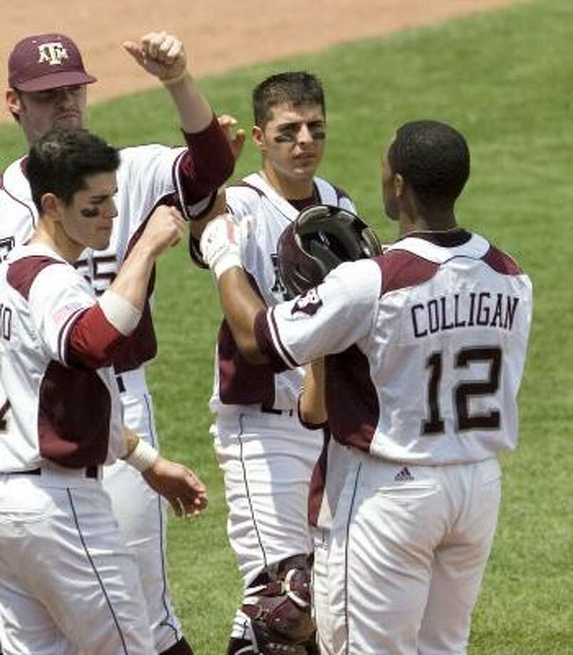 """The Aggies greet Kyle Colligan after he """"accidentally"""" hit another of his home runs. Photo: ALONZO ADAMS, ASSOCIATED PRESS"""