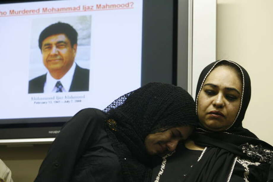 Sobia Ijaz is comforted by her mother, Qudsia Ijaz, as they stand in front of a projected image of their father and husband, Mohammad Ijaz Mahmood, during a news conference seeking help in finding his killers. Photo: Nathan Lindstrom, For The Chronicle