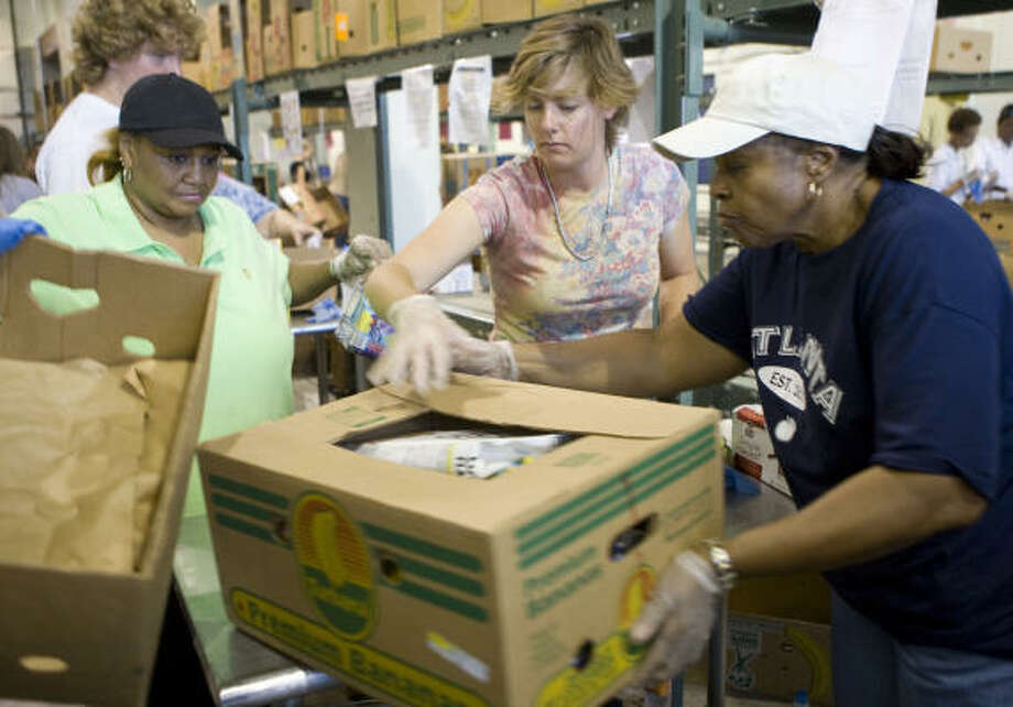 Georgia Lewis, left, Morgan Whitney and Valleda Crump help to unload and sort through boxes of donated food items on Sept. 17 at the Houston Food Bank, 3811 Eastex Freeway, in the wake of Hurricane Ike. Photo: Jason Brown