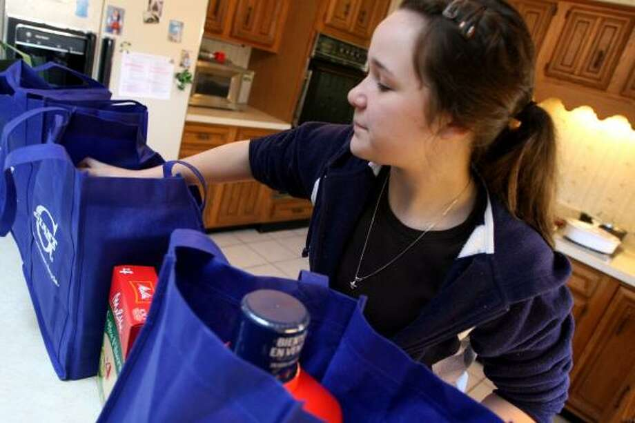 Samantha Kobor, 14, who learned about inflation in fourth grade, unloads groceries at her Great Falls, Va., home. She says her allowance of up to $20 a week doesn't go as far as it once did. Photo: Lois RAIMONDO, WASHINGTON POST