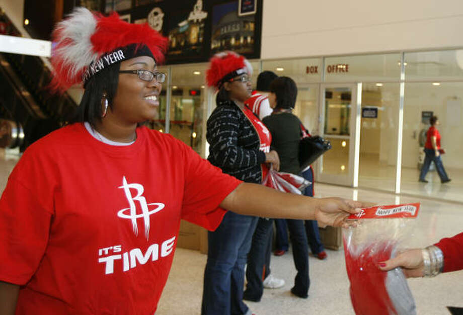 Fans flipped for a wig giveaway at Toyota Center. Here Keionna Sanders gives out the freebies. Photo: James Nielsen, Chronicle