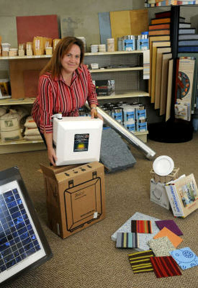 Angelique Grado shows off some of her new green products, including a Seisco tankless water heater, a solar attic fan, an LED recessed lighting fixture, and some Flor carpet tiles at the Green Builders Source store in Oak Ridge North on May 12. Photo: Jerry Baker, For The Chronicle