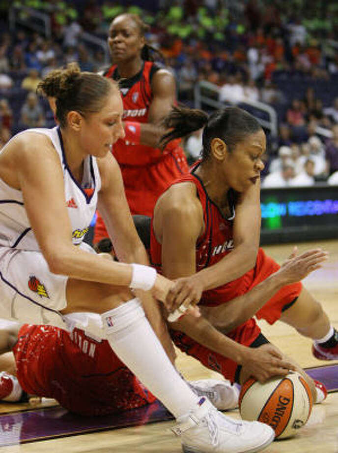 Comets' Tina Thompson, right, and Tamecka Dixon, bottom on floor, battle Phoenix Mercury guard Diana Taurasi, left, for a loose ball in a game earlier this month. Photo: Ross D. Franklin, AP